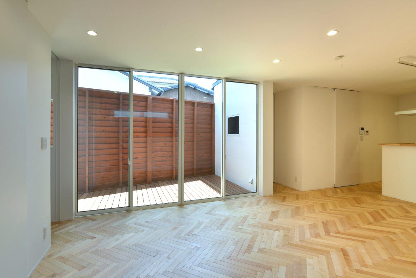 ヘリンボーンの床材が印象的なリビング
